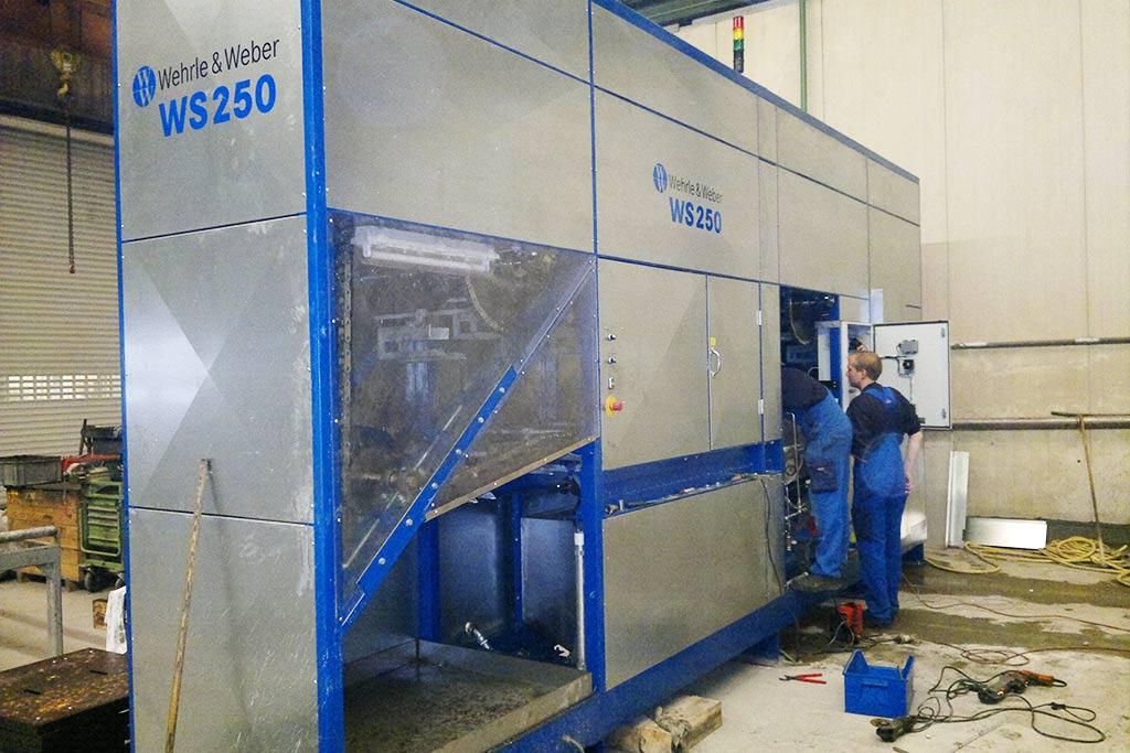 Reinigungsanlage für einen Bahnschwellen Hersteller. Hier werden die ausgehärteten Betonanhaftungen der Bauteile vom Fertigungsprozess automatisch zur Wiederverwendung gereinigt.